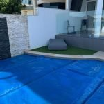 Synthetic outdoor grass mat around pool